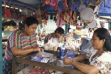 Fotografía de vendedora ofreciendo productos en una feria en Antigua, Guatemala.